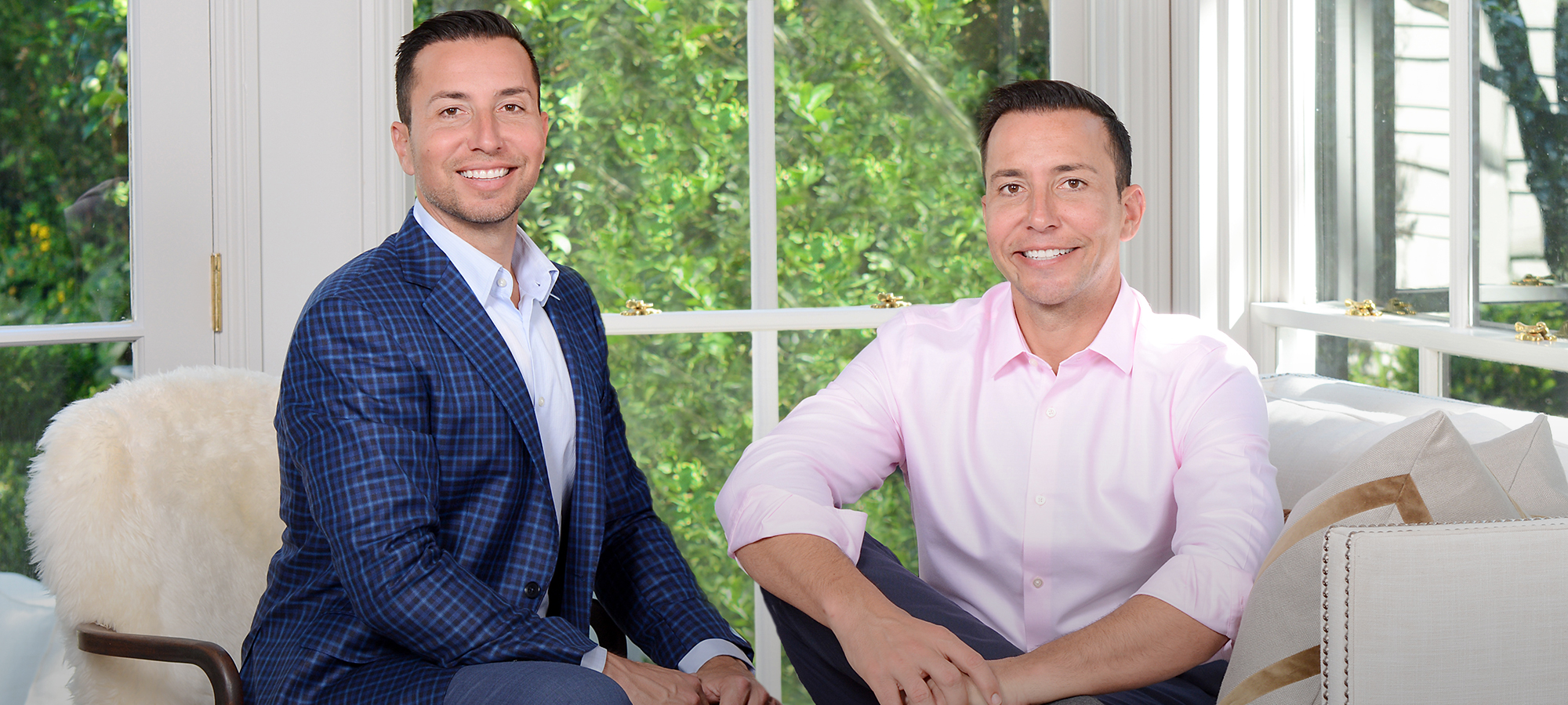 Principals, Chris and Rob Desino, sitting in a sunroom with greenery behind them