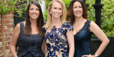 Realtors, Olga Page and Mary Lou Wertz, standing behind Broker-In-Charge, Leslie Turner